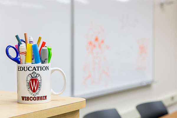 """mug with """"education"""" text full of pens and markers in front of whiteboard"""